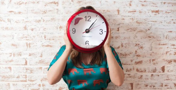 cirkadianní rytmus - obrázek ženy držící hodiny před obličejem